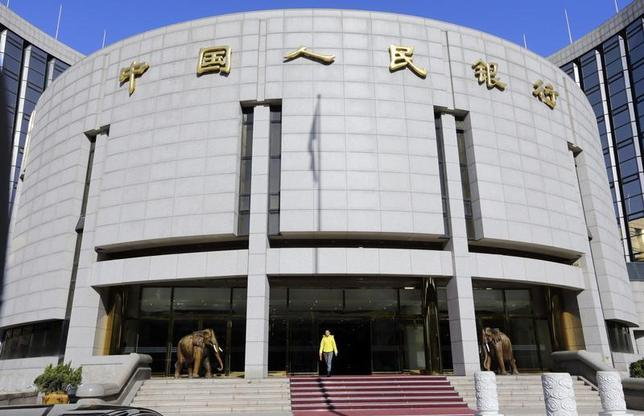A woman walks out of the headquarters of the People's Bank of China (PBOC), the central bank, in Beijing November 20, 2013. REUTERS/Jason Lee