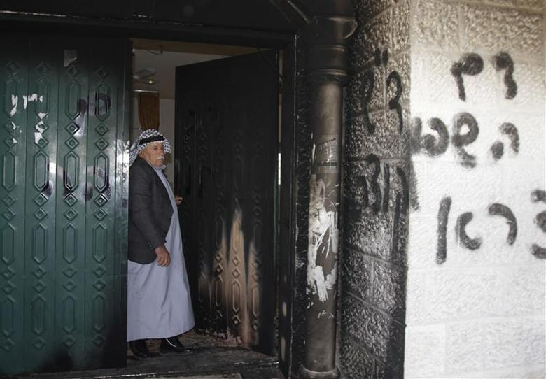 A Palestinian man stands near a door and wall of a mosque which were vandalised in the West Bank village of Deir Istiya, near the Jewish settlement of Ariel January 15, 2014. REUTERS/Abed Omar Qusini