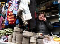 Продавщица говорит по телефону на рынке в Волгограде 4 января 2014 года. Потребительские цены в РФ выросли за период с 1 по 13 января 2014 года на 0,3 процента, сообщил Росстат. REUTERS/Vasily Fedosenko REUTERS/Vasily Fedosenko
