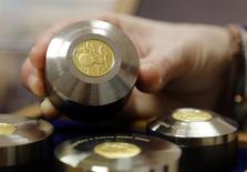 An employee of Editalia shows a gold mint of one Italian lira as part of a coin collection in Rome, January 14, 2014. REUTERS/Stefano Rellandini