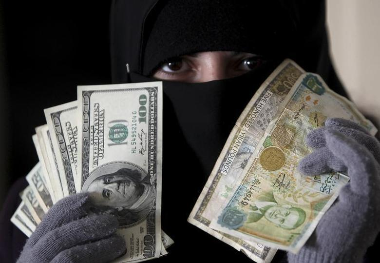 A woman shows U.S. dollars and Syrian pounds in Amman December 12, 2011. REUTERS/Ali Jarekji