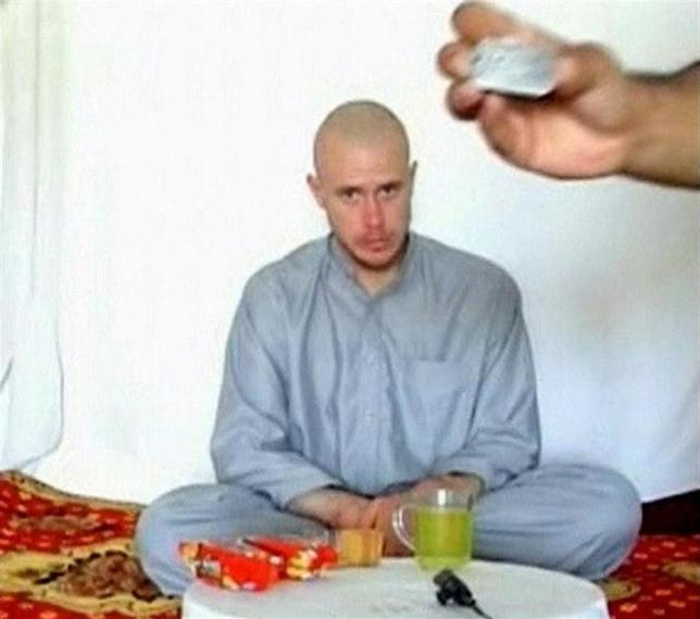 U.S. Army Private Bowe Bergdahl watches as one of his captors displays his identity tag to the camera at an unknown location in Afghanistan, in this file photo taken July 19, 2009. REUTERS/via Reuters TV