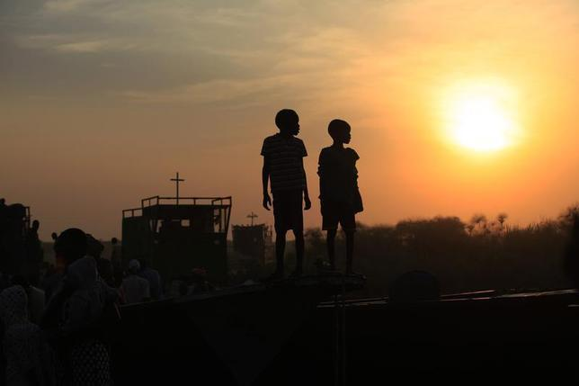 Children displaced by the fighting in Bor county, who have just arrived, are standing on the side of a boat in the port in Minkaman, in Awerial county, Lakes state, in South Sudan, January 15, 2014. REUTERS/Andreea Campeanu