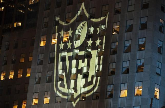 A man stands at a window lit by the NFL logo as he watches performances during the 2012 NFL kickoff show in New York September 5, 2012. REUTERS/Lucas Jackson