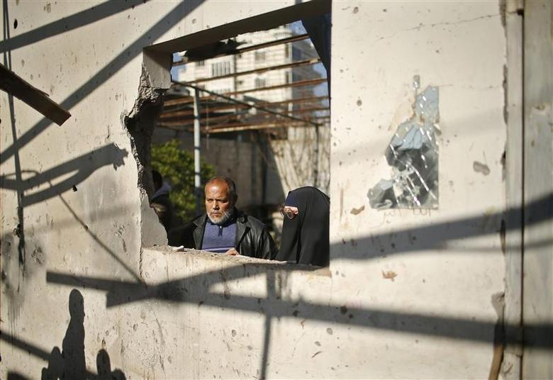Palestinians inspect their house yard, which they said was hit in an Israeli air strike, in Gaza City January 16, 2014. REUTERS/Mohammed Salem