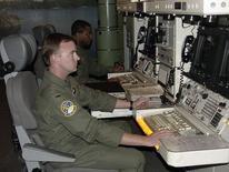 Офицеры ВВС США сидят за командным пультом в центре управления пусками в Монтане 22 августа 2005 года. Командование ВВС США временно лишило допуска к секретной информации три десятка офицеров и проводит переэкзаменовку всего подразделения, отвечающего за ядерную безопасность страны, после того как стало известно о масштабных списываниях во время ключевого теста на профпригодность. REUTERS/Adam Tanner