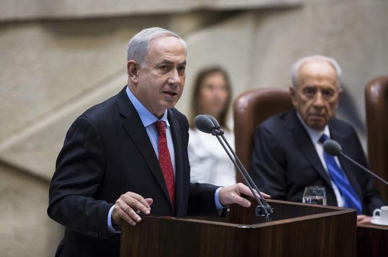 Israel's Prime Minister Benjamin Netanyahu (L) delivers a speech during a session marking the 65th anniversary of the Knesset, the Israeli parliament, in Jerusalem January 14, 2014, at the beginning of the second winter session of the Knesset. REUTERS/Baz Ratner