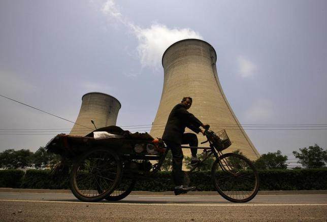 A man rides his tricycle past the cooling tower and chimneys from a coal-burning power station in Beijing June 1, 2012. REUTERS/David Gray