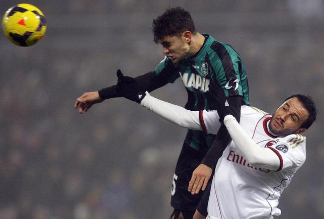 AC Milan's Giampaolo Pazzini (R) jumps for the ball with Sassuolo's Luca Antei during their Italian Serie A soccer match at the Mapei stadium in Reggio Emilia January 12, 2014. REUTERS/Alessandro Garofalo