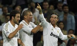 Real Madrid's Gonzalo Higuain (L) and Pepe congratulate teammate Sergio Ramos (R) after scoring a goal against Olympique Lyon during their Champions League soccer match at the Santiago Bernabeu stadium in Madrid, October 18, 2011. REUTERS/Juan Medina