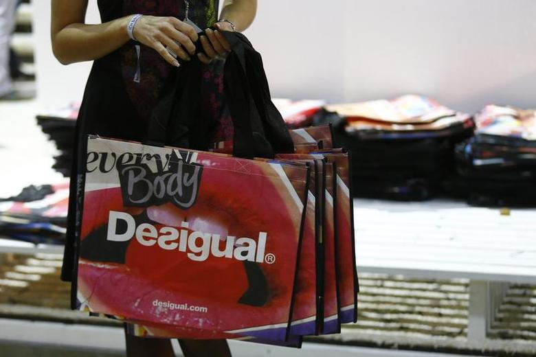 A woman hands out bags at the booth of Spanish fashion brand Desigual at the Bread and Butter fashion trade show at the former Tempelhof airport in Berlin. REUTERS/Tobias Schwarz