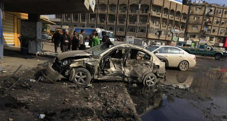People gather at the site of a car bomb attack in Baghdad, January 15, 2014. REUTERS/Ahmed Saad