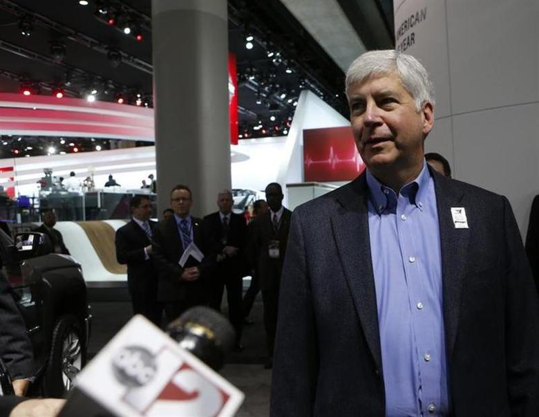 Michigan Governor Rick Snyder (R-MI) is interviewed as he tours the display floor during the press preview day of the North American International Auto Show in Detroit, Michigan January 14, 2014. REUTERS/Rebecca Cook