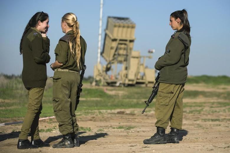Israeli soldiers stand in front of the launcher of an Iron Dome missile interceptor battery deployed in the southern Israeli coastal city of Ashkelon January 16, 2014. REUTERS/Amir Cohen