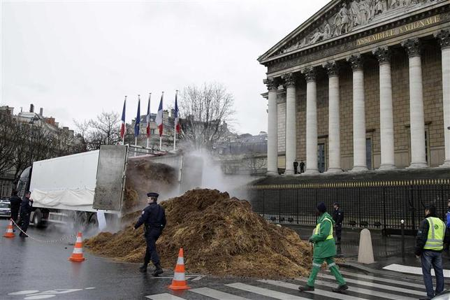 French police and municipal workers walk near a large pile of manure sitting in front of the National Assembly in Paris January 16, 2014. REUTERS/Jacky Naegelen
