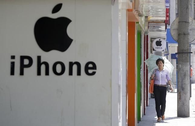 A woman walks past a logo of Apple Inc in Wuhan, Hubei province July 24, 2013. REUTERS/Darley Shen