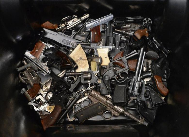 A pile of handguns are placed in a trash bin after they were surrendered during a gun buyback program organized by Mayor Eric Garcetti's Gang Reduction and Youth Development Office in Los Angeles, California, December 14, 2013. REUTERS/Kevork Djansezian