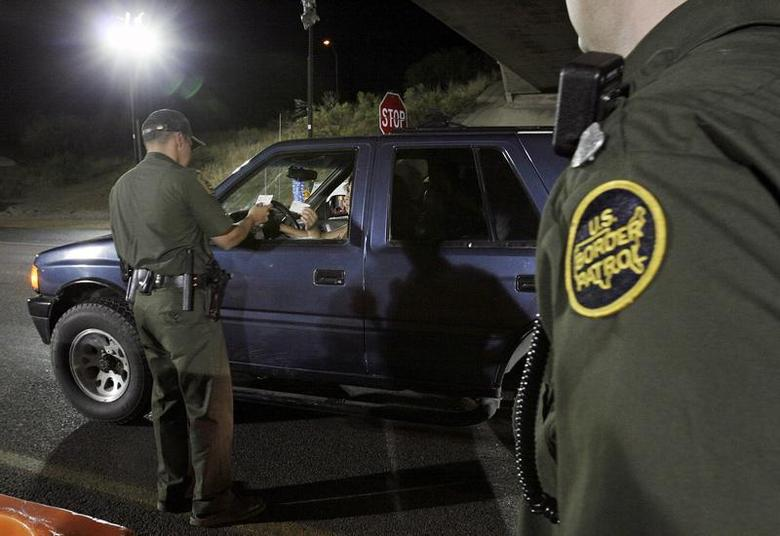 A U.S. Border Patrol agent checks the identification of a motorist at a checkpoint 20 miles north of the United States and Mexican border near Tubac, Arizona, May 21, 2006. REUTERS/Jeff Topping -