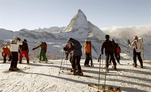 Skiers stand in front of Matterhorn mountain at Gornergrat in the ski resort of Zermatt December 14, 2010. REUTERS/Arnd Wiegmann/Files
