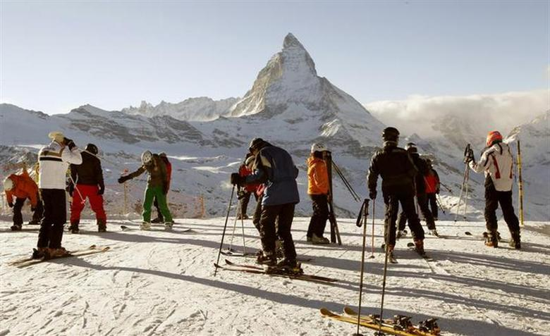 Skiers stand in front of Matterhorn mountain at Gornergrat in the ski resort of Zermatt December 14, 2010. REUTERS/Arnd Wiegmann/Files