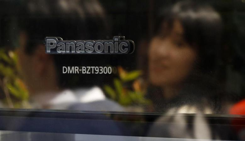 Passers-by are reflected on a product of Panasonic Corp outside an electronics store in Tokyo May 9, 2013. REUTERS/Toru Hanai