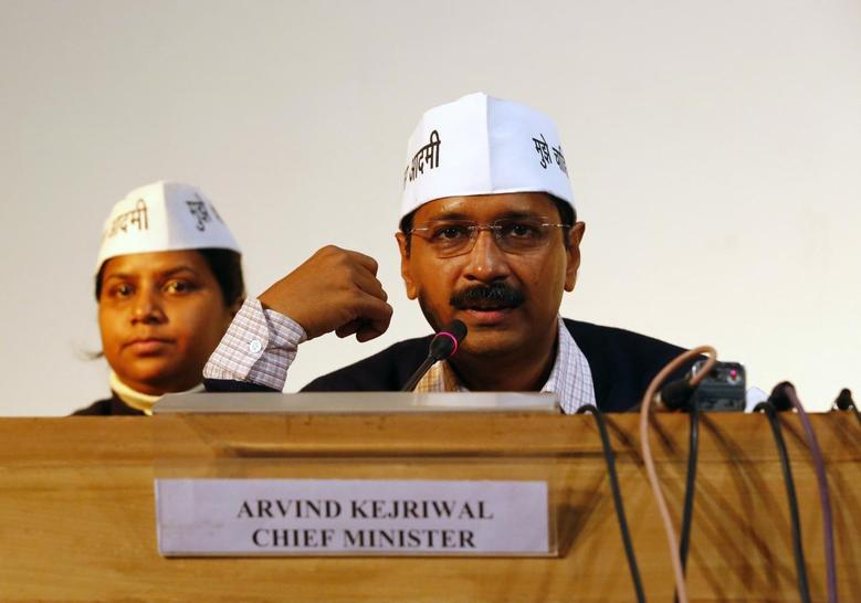 Arvind Kejriwal (R), leader of Aam Aadmi (Common Man) Party, speaks during a meeting with his party leaders and media personnel after taking the oath as the new chief minister of Delhi, in New Delhi December 28, 2013. REUTERS/Anindito Mukherjee