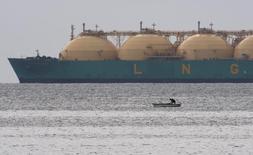 Рыбацкая лодка на фоне СПГ-танкера близ Гаваны 28 июня 2009 года. Аляска подписала соглашение с крупными нефтегазовыми компаниями о строительстве газопровода для доставки газа на предполагаемый завод по его сжижению для экспорта в Азию. REUTERS/Desmond Boylan