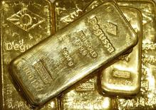 Слитки золота в хранилище трейдера драгоценными металлами Degussa в Цюрихе 19 апреля 2013 года. Цены на золото стабильны и могут упасть за неделю впервые за четыре недели, так как данные из США указывают на стабильный рост американской экономики, что снижает привлекательность золота как низкорискованного вложения. REUTERS/Arnd Wiegmann