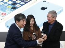 Apple Inc. CEO Tim Cook (R) and China Mobile's Chairman Xi Guohua (L) with iPhones pose with a customer at an event celebrating the launch of Apple's iPhone on China Mobile's network at a China Mobile shop in Beijing January 17, 2014. REUTERS/Kim Kyung-Hoon