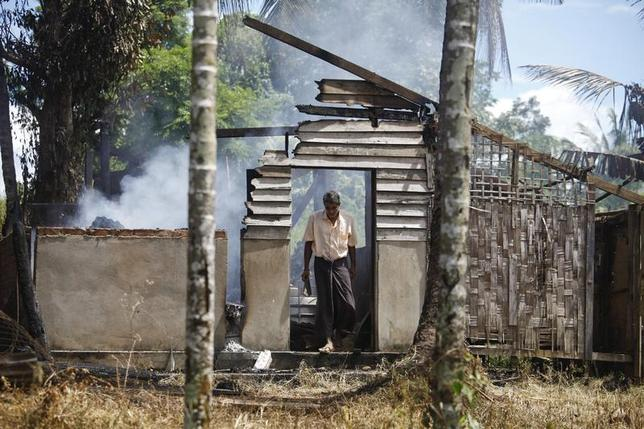 A man walks out from a destroyed mosque that was burnt down in recent violence at Thapyuchai village, outside of Thandwe, in the Rakhine state, October 3, 2013. REUTERS/Soe Zeya Tun