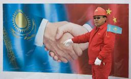 Китайский рабочий стоит на фоне плаката во время церемонии запуска под Алма-Атой казахстанского участка газопровода из Туркмении в КНР 12 декабря 2009 года. Китайская нефтяная компания China National Petroleum Corporation повысила добычу нефти и газа за рубежом на 12,9 процента в прошлом году, значительно ускорив рост по сравнению с 2012 годом. REUTERS/Shamil Zhumatov