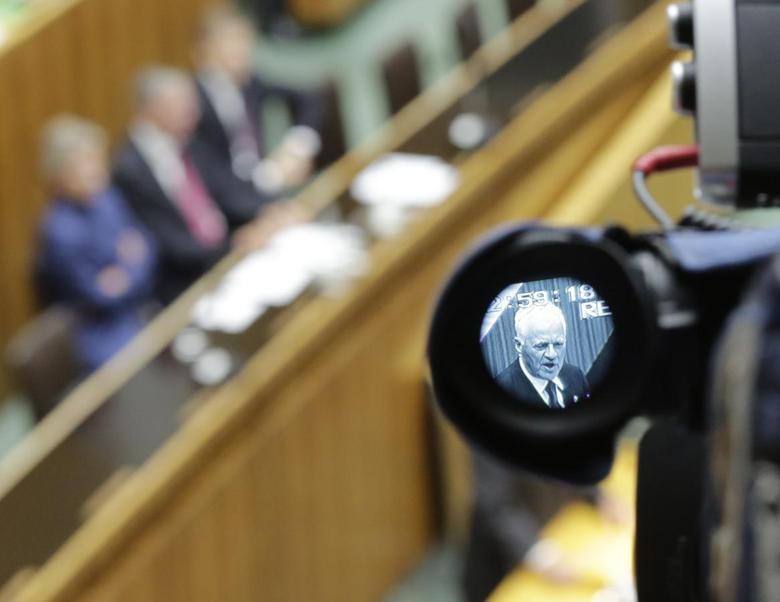 Austro-Canadian businessman and billionaire Frank Stronach is seen through the viewfinder of a camera as he delivers his first speech during constitutional session of the parliament following general elections in Vienna October 29, 2013. REUTERS/Leonhard Foeger