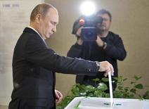 Владимир Путин опускает бюллетень на избирательном участке № 2151 на выборах мэра Москвы 8 сентября 2013 года. Послушная Кремлю Госдума в пятницу приняла в первом чтении законопроект, возвращающий гражданам отменённое в нулевые право голосовать против всех, если это не президентские выборы, сообщили госинформагентства. REUTERS/Alexei Druzhinin/RIA Novosti/Kremlin