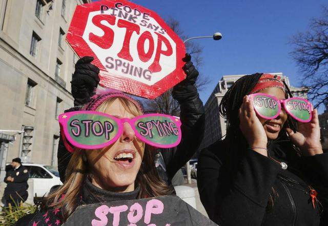 The founder of the protest group Code Pink Medea Benjamin (L) protests against U.S. President Barack Obama and the NSA before his arrival at the Department of Justice in Washington, January 17, 2014. REUTERS/Larry Downing