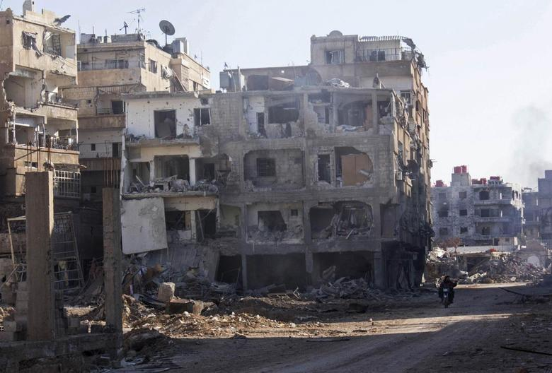 Men ride a motorbike past buildings damaged by what activists said was shelling by forces loyal to Syria's President Bashar al-Assad in Daraya, near Damascus January 15, 2014. REUTERS/Hussam Zeen
