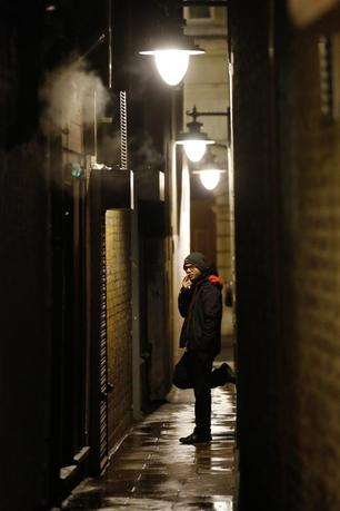 A man smokes in an alley behind his place of work in London January 17, 2014. REUTERS/Luke MacGregor