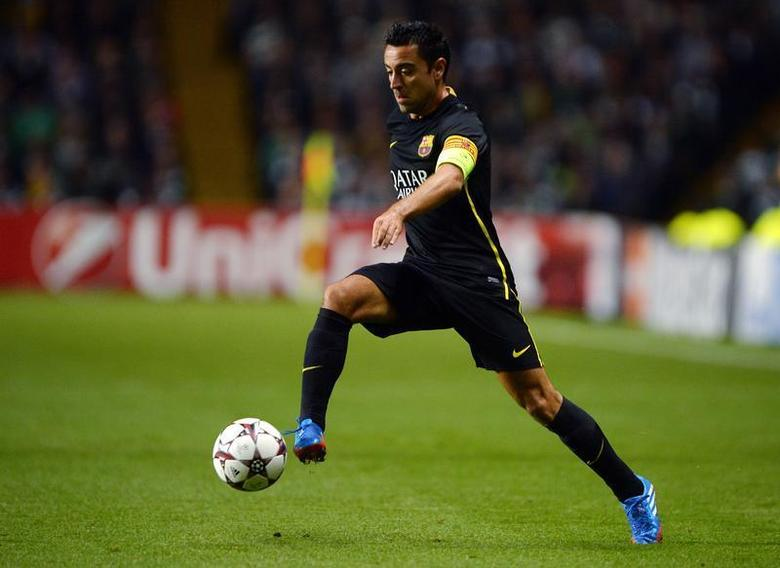 Barcelona's Xavi Hernandez runs with the ball during their Champions League soccer match against Celtic at Celtic Park in Glasgow, October 1, 2013. REUTERS/Russell Cheyne