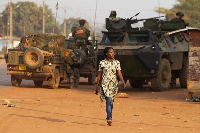 A woman walks past French peacekeeping troops in a street of the capital Bangui January 17, 2014. REUTERS/Siegfried Modola