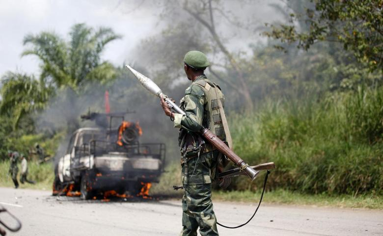 A Congolese soldier from the Armed Forces of the Democratic Republic of Congo (FARDC) looks at their burning vehicle after an ambush near the village of Mazizi in North Kivu province January 2, 2014. REUTERS/Kenny Katombe