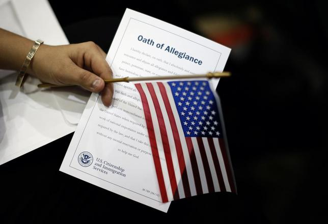 A woman holds the Oath of Allegiance at a naturalization ceremony for 3,703 new U.S. citizens from 130 countries, in Los Angeles, California, December 17, 2013. REUTERS/Lucy Nicholson