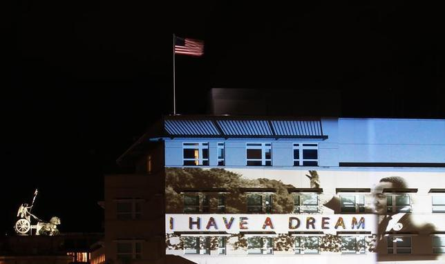 A light installation showing Martin Luther King Jr. is projected on the facade of the U.S. Embassy, next to the Quadriga (L) atop of the Brandenburg Gate, during the ''Festival of Light'' show in Berlin October 17, 2013 file photo. REUTERS/Thomas Krumenacker