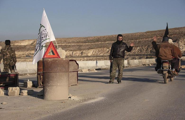A member of al-Jabha al-Islamiya (the Islamic Front) mans a checkpoint between the village of Kafaroumeh and the town of Maaret al-Naaman, to prevent members of the al Qaeda-affiliated Islamic State of Iraq and the Levant (ISIL) from advancing towards Jabal Al-Zawiya, in Idlib January 6, 2014. REUTERS/Fadi Mashan