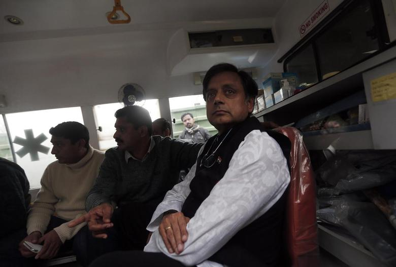 India's Minister of State for Human Resource Development Shashi Tharoor (R) sits in an ambulance as he waits outside a mortuary to receive his wife Sunanda Puskhar Tharoor's body at a hospital in New Delhi January 18, 2014. REUTERS/Adnan Abidi