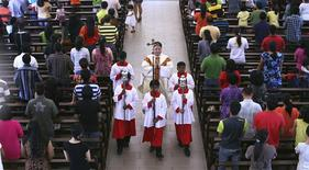 A priest and altar boys walk down the aisle after prayers were conducted during a mass service inside the church of Our Lady of Lourdes at Klang, outside Kuala Lumpur January 12, 2014. REUTERS/Samsul Said (