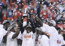 Denver Broncos players hold up the Lamar Hunt Trophy after they defeated the New England Patriots in the NFL's AFC Championship football game in Denver, January 19, 2014. REUTERS/Mark Leffingwell