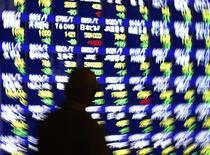 Мужчина смотрит на экран с фондовыми котировками у брокерской конторы в Токио 14 января 2014 года. Азиатские фондовые рынки, кроме Южной Кореи, снизились в понедельник под давлением китайской статистики и укрепления иены. REUTERS/Issei Kato