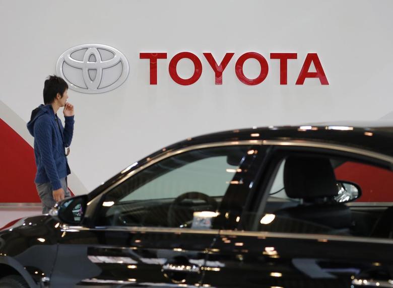 A man walks past Toyota Motor's logo at the company's showroom in Tokyo November 6, 2013. REUTERS/Toru Hanai