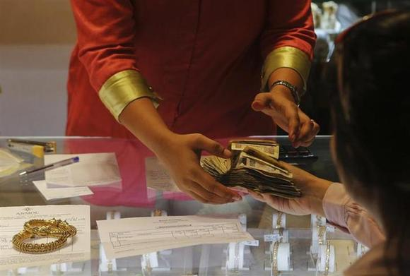 An employee receives payment from a customer inside a gold jewellery showroom in Mumbai August 30, 2013. REUTERS/Danish Siddiqui/files