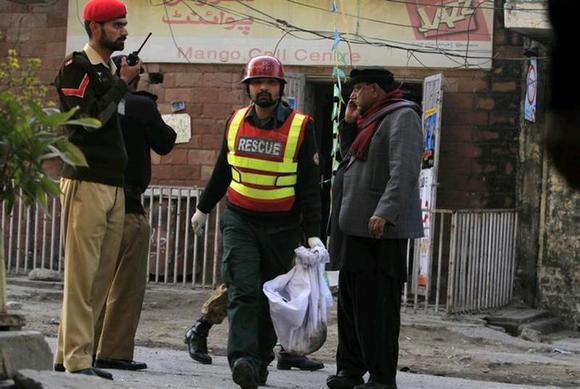A rescue worker collects evidence from the site of a suicide blast in Rawalpini January 20, 2014. REUTERS/Faisal Mahmood