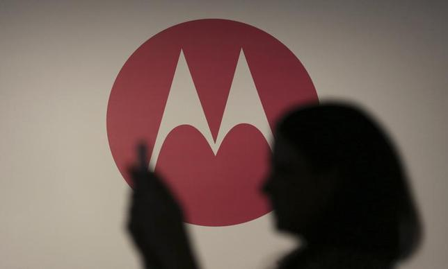 A woman takes a picture in front of a Motorola logo before the worldwide presentation of the Moto G mobile phone in Sao Paulo November 13, 2013. REUTERS/Nacho Doce/Files